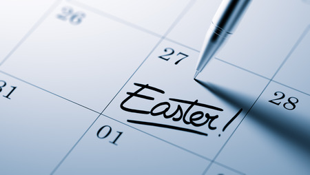written date: Closeup of a personal agenda setting an important date written with pen. The words Easter written on a white notebook to remind you an important appointment.