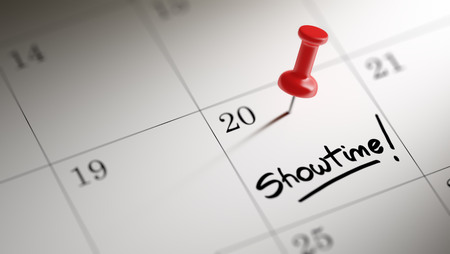 showtime: Concept image of a Calendar with a red push pin. Closeup shot of a thumbtack attached. The words Showtime written on a white notebook to remind you an important appointment.