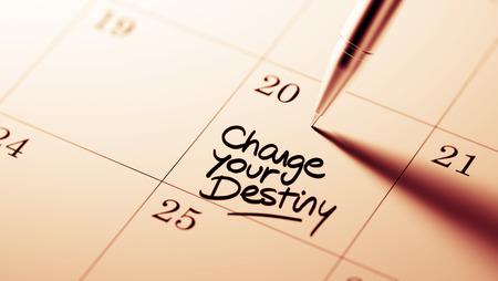 Closeup of a personal agenda setting an important date written with pen. The words Change your destiny written on a white notebook to remind you an important appointment. Stock Photo
