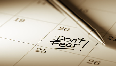 dont: Closeup of a personal agenda setting an important date written with pen. The words Dont Fear written on a white notebook to remind you an important appointment.
