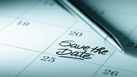 written date: Closeup of a personal agenda setting an important date written with pen. The words Save the date written on a white notebook to remind you an important appointment. Stock Photo