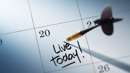 living moment: Concept image of a Calendar with a golden dart stick. The words Live today written on a white notebook to remind you an important appointment.