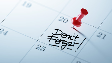 Concept image of a Calendar with a red push pin. Closeup shot of a thumbtack attached. The words Don`t Forget written on a white notebook to remind you an important appointment. Stock Photo