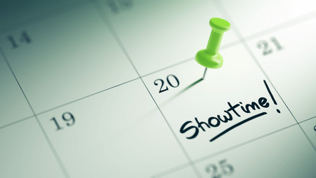 showtime: Concept image of a Calendar with a green push pin. Closeup shot of a thumbtack attached. The words Showtime written on a white notebook to remind you an important appointment. Stock Photo