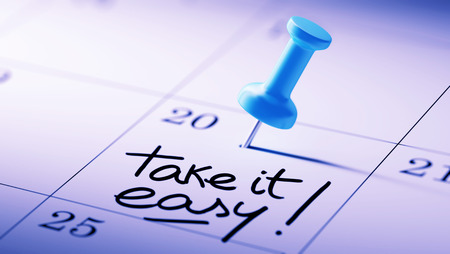 take it easy: Concept image of a Calendar with a blue push pin. Closeup shot of a thumbtack attached. The words Take it easy written on a white notebook to remind you an important appointment.