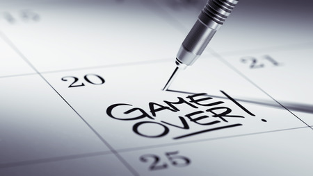 the game is over: Concept image of a Calendar with a golden dart stick. The words Game over written on a white notebook to remind you an important appointment.