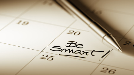 written date: Closeup of a personal agenda setting an important date written with pen. The words Be Smart written on a white notebook to remind you an important appointment.