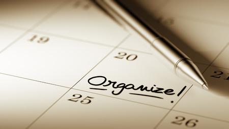 Close-up van een persoonlijke agenda instellen van een belangrijke datum geschreven met pen. De woorden Organiseren geschreven op een witte laptop om u te herinneren van een belangrijke afspraak.