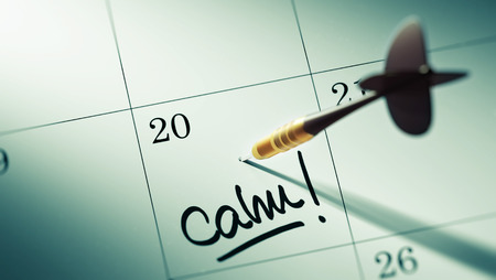 reflexive: Concept image of a Calendar with a golden dart stick. The words Calm written on a white notebook to remind you an important appointment.