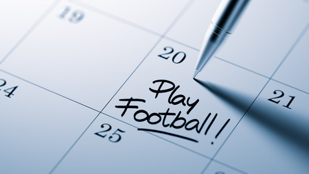 play date: Closeup of a personal agenda setting an important date written with pen. The words Play Football written on a white notebook to remind you an important appointment.