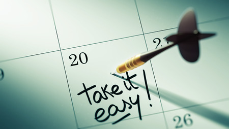 take it easy: Concept image of a Calendar with a golden dart stick. The words Take it easy written on a white notebook to remind you an important appointment.