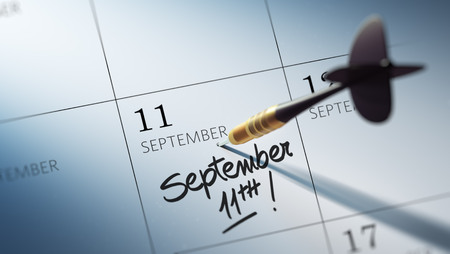 11th: Concept image of a Calendar with a golden dart stick. The words September 11th written on a white notebook to remind you an important appointment.