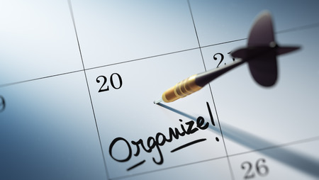 organize: Concept image of a Calendar with a golden dart stick. The words Organize written on a white notebook to remind you an important appointment. Stock Photo