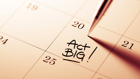 important date: Closeup of a personal agenda setting an important date written with pen. The words Act BIG written on a white notebook to remind you an important appointment.