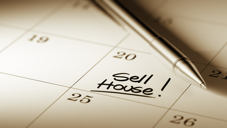 sell house: Closeup of a personal agenda setting an important date written with pen. The words Sell House written on a white notebook to remind you an important appointment. Stock Photo