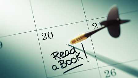 appointment book: Concept image of a Calendar with a golden dart stick. The words Read a book written on a white notebook to remind you an important appointment.