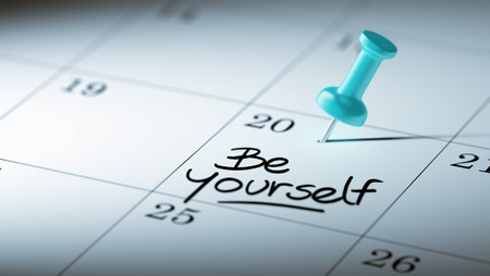 be yourself: Concept image of a Calendar with a blue push pin. Closeup shot of a thumbtack attached. The words be yourself written on a white notebook to remind you an important appointment.