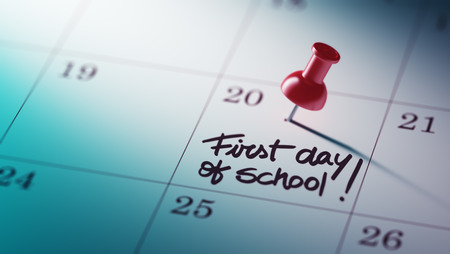 Concept image of a Calendar with a red push pin. Closeup shot of a thumbtack attached. The words First day of school written on a white notebook to remind you an important appointment. Stock Photo