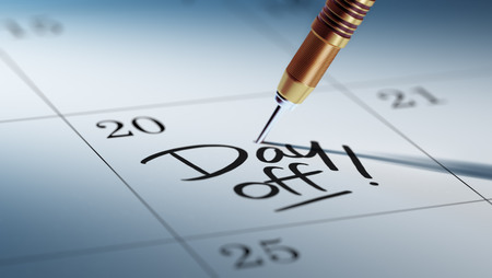 Concept image of a Calendar with a golden dart stick. The words Day off written on a white notebook to remind you an important appointment. Stock Photo