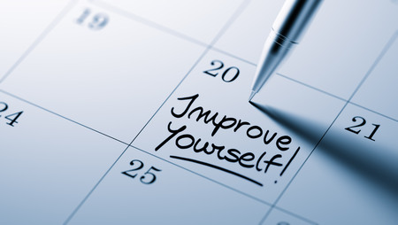 better days: Closeup of a personal agenda setting an important date written with pen. The words Improve yourself written on a white notebook to remind you an important appointment. Stock Photo