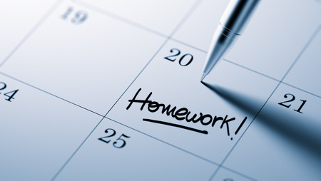 important date: Closeup of a personal agenda setting an important date written with pen. The words Homework written on a white notebook to remind you an important appointment.