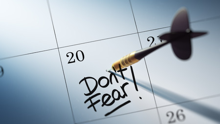 dont: Concept image of a Calendar with a golden dart stick. The words Dont Fear written on a white notebook to remind you an important appointment.