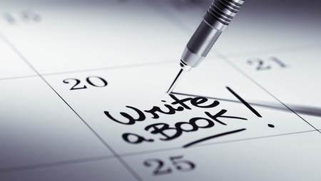 appointment book: Concept image of a Calendar with a golden dart stick. The words Write a Book written on a white notebook to remind you an important appointment. Stock Photo