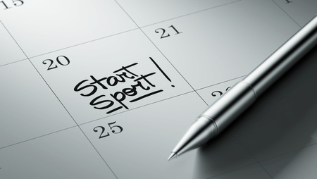 written date: Closeup of a personal agenda setting an important date written with pen. The words Start Sport written on a white notebook to remind you an important appointment. Stock Photo