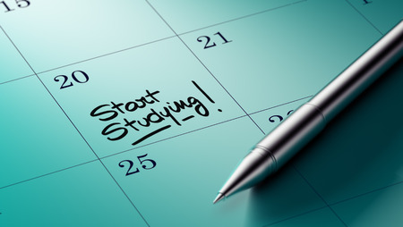 written date: Closeup of a personal agenda setting an important date written with pen. The words Start Studying written on a white notebook to remind you an important appointment. Stock Photo