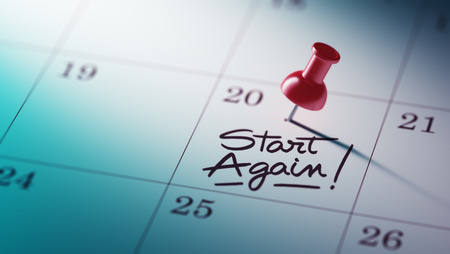 Concept image of a Calendar with a red push pin. Closeup shot of a thumbtack attached. The words Start Again written on a white notebook to remind you an important appointment.