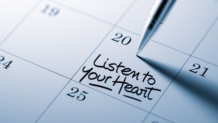 written date: Closeup of a personal agenda setting an important date written with pen. The words Listen to your heart written on a white notebook to remind you an important appointment.