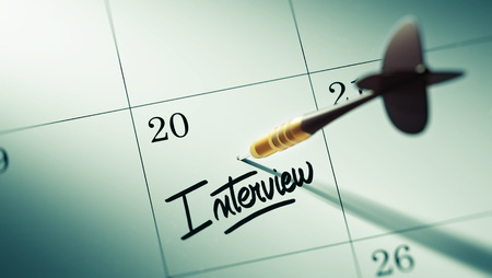oral communication: Concept image of a Calendar with a golden dart stick. The words Interview written on a white notebook to remind you an important appointment. Stock Photo