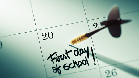 first day: Concept image of a Calendar with a golden dart stick. The words First day of school written on a white notebook to remind you an important appointment. Stock Photo