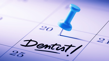 reminder: Concept image of a Calendar with a blue push pin. Closeup shot of a thumbtack attached. The words Dentist! written on a white notebook to remind you an important appointment.