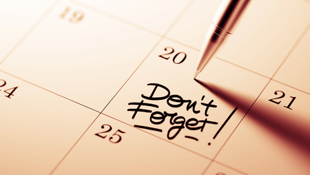 dont: Closeup of a personal agenda setting an important date written with pen. The words Don`t Forget written on a white notebook to remind you an important appointment. Stock Photo