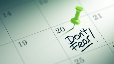 dont: Concept image of a Calendar with a green push pin. Closeup shot of a thumbtack attached. The words Dont Fear written on a white notebook to remind you an important appointment. Stock Photo