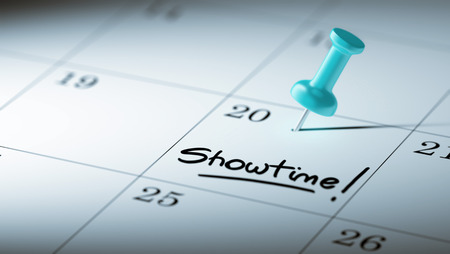 showtime: Concept image of a Calendar with a blue push pin. Closeup shot of a thumbtack attached. The words Showtime written on a white notebook to remind you an important appointment.