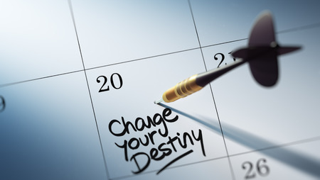 Concept image of a Calendar with a golden dart stick. The words Change your destiny written on a white notebook to remind you an important appointment. Stock Photo