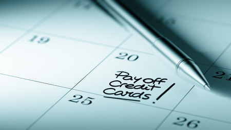 pay off: Closeup of a personal agenda setting an important date written with pen. The words Pay off Credit cards written on a white notebook to remind you an important appointment.