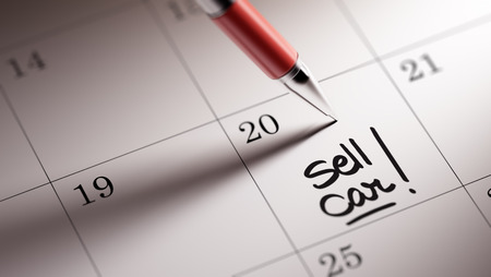 written date: Closeup of a personal agenda setting an important date written with pen. The words Sell Car written on a white notebook to remind you an important appointment. Stock Photo