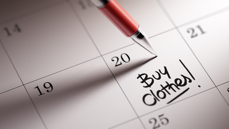 clothes organizer: Closeup of a personal agenda setting an important date written with pen. The words Buy Clothes written on a white notebook to remind you an important appointment.
