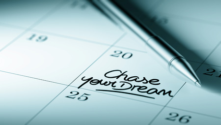chase: Closeup of a personal agenda setting an important date written with pen. The words Chase your dream written on a white notebook to remind you an important appointment.