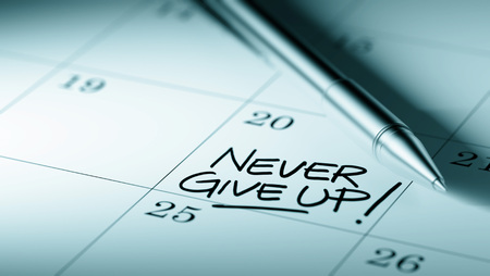 up to date: Closeup of a personal agenda setting an important date written with pen. The words Never give up written on a white notebook to remind you an important appointment. Stock Photo