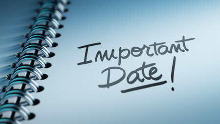 written date: Closeup of a personal calendar setting an important date representing a time schedule. The words Important date written on a white notebook to remind you an important appointment.