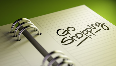 go to the shopping: Closeup of a personal agenda setting an important date representing a time schedule. The words Go shopping written on a white notebook to remind you an important appointment. Stock Photo