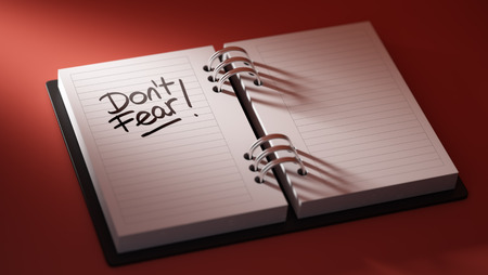 Closeup of a personal agenda setting an important date representing a time schedule. The words Dont Fear written on a white notebook to remind you an important appointment. Stock Photo