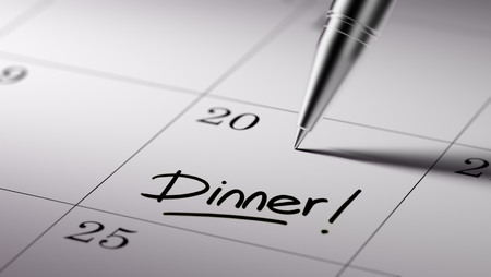 written date: Closeup of a personal agenda setting an important date written with pen. The words Dinner written on a white notebook to remind you an important appointment.