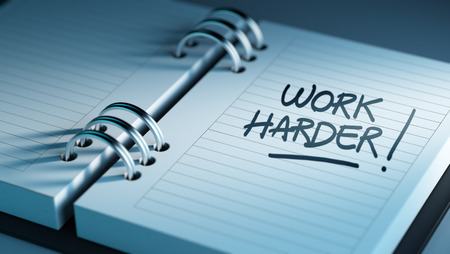 harder: Closeup of a personal agenda setting an important date representing a time schedule. The words Work Harder written on a white notebook to remind you an important appointment. Stock Photo