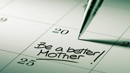 mother to be: Closeup of a personal agenda setting an important date written with pen. The words Be a better mother written on a white notebook to remind you an important appointment.