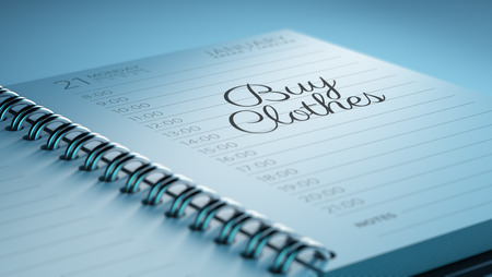 clothes organizer: Closeup of a personal calendar setting an important date representing a time schedule. The words Buy Clothes written on a white notebook to remind you an important appointment. Stock Photo